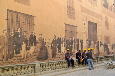Road workers near the historical painted wall in Havana Editorial