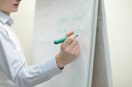 person writing: A person writing on flip chart desk.