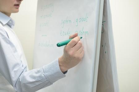 Une personne qui écrit sur le tableau de bureau flip. Banque d'images
