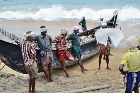 pescador: Los pescadores cerca de la embarcación en la playa de Kovalama India.