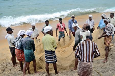 pescador: Pescadores tradicionales est�n tirando de la red de pesca de cerco del mar, en la playa de Kovalam.