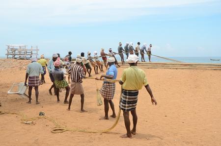 pescador: Pescadores tradicionales están tirando de la red de pesca de cerco del mar, en la playa de Kovalam.