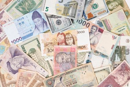Muchas monedas diferentes como concepto de fondo colorido dinero global Foto de archivo