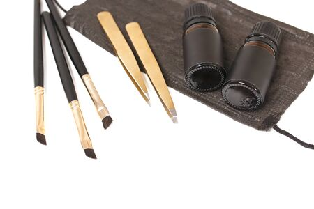 Tools for eyebrow shaping. Mask, tweezers, brushes. Top view, place for text. White background.