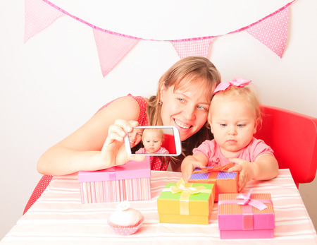 mother and little daughter taking mobile photo at birthday party photo