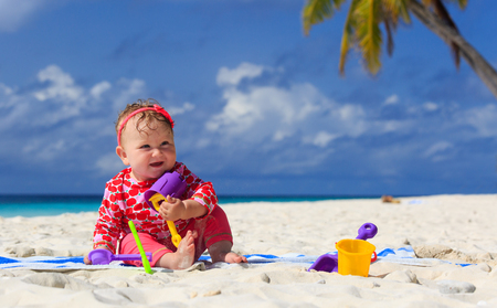 little girl playing with sand on tropical beach photo