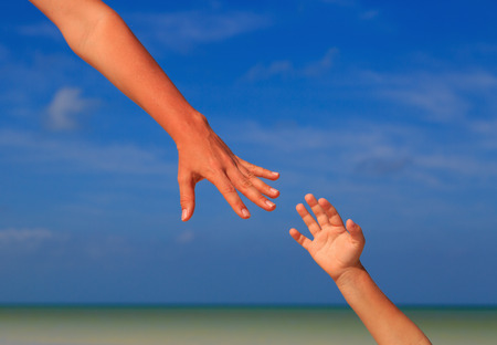 child protection: helping hand of mother and child on sky at the beach, care and protection