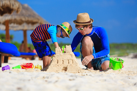 father and son building sand castle on tropical sand beach photo