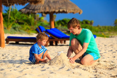 dad and child: father and son building sand castle on tropical sand beach