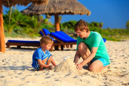 verano: padre e hijo edificio castillos de arena en la playa tropical de la arena