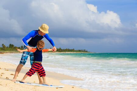 father and little son learning surfing at summer beach photo