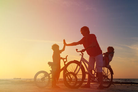 niños en bicicleta: Biker silueta de la familia, padre de dos niños en bicicleta al atardecer