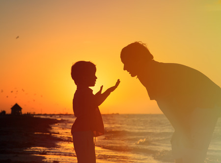 father and little son talking at sunset beach Imagens