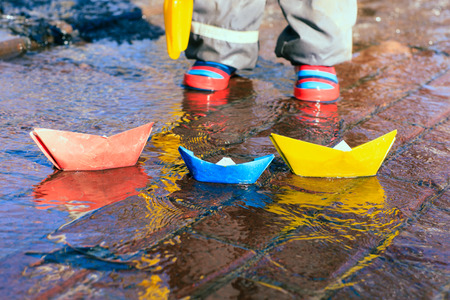 child playing with paper boats in spring water puddle Stock Photo