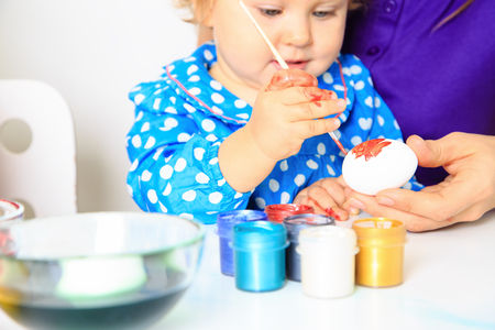 mother and little daughter painting eggs, easter holiday photo