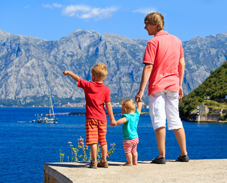 father with two kids hiking in summer mountains photo