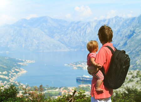 father with little daughter looking at mountains on vacation photo
