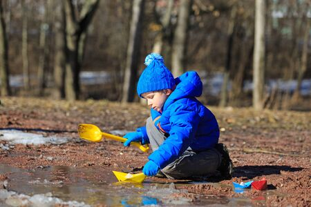 interst: little boy plaing with paper boats in spring puddle outdoors Stock Photo