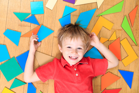 happy little boy with puzzle toys on wooden floor, early learning Imagens