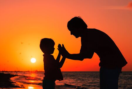 fun day: father and son playing at sunset sea