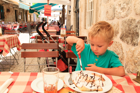 cute little boy eating in city cafe on summer day photo