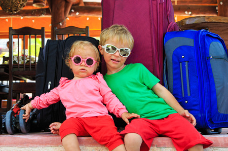 family with two children: little boy and toddler girl sitting on suitcases ready to travel, kids travel