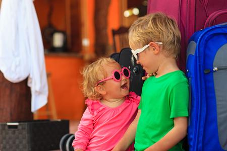 femme valise: petit gar�on et b�b� fille assise sur des valises pr�tes � voyager, les enfants voyagent