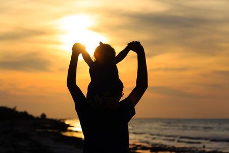 padre e hija: padre e hija se divierten en la playa de la puesta del sol