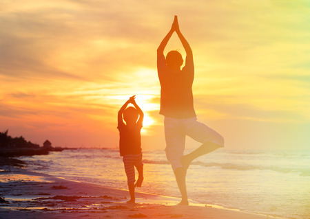 father and son doing yoga at sunset sea photo