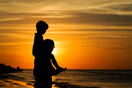 father and son on shoulders looking at sunset on the beach