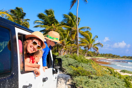 holiday trip: family driving off-road car on tropical beach, vacation concept