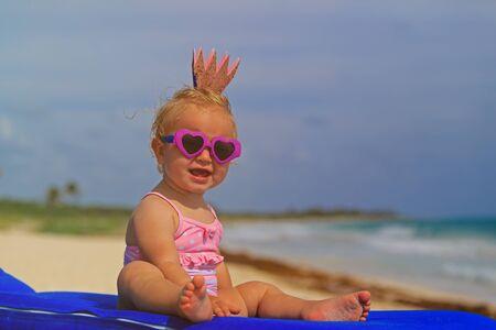 cute little baby princess on summer tropical beach photo
