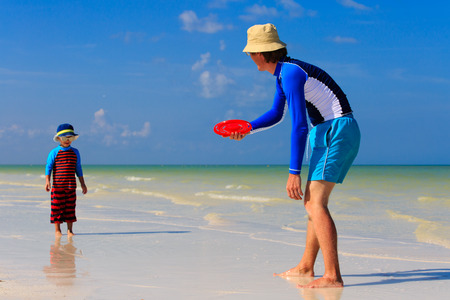 flying disc: Father and son playing with flying disc at tropical beach
