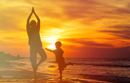 silhouettes of father and son doing yoga at sunset sea photo