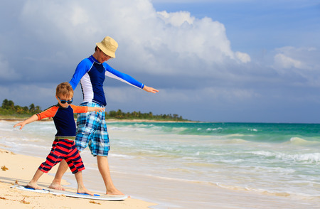 father and little son practicing surfing positin at summer beach photo