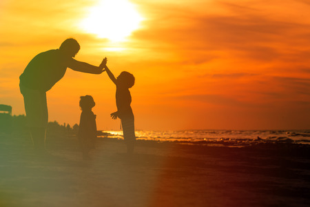 father and two kids, boy and girl, playing at sunset beach