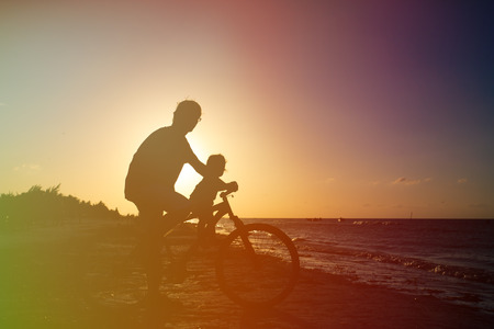 little girl beach: Silhouette of father and baby biking at sunset sea