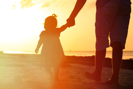 Silhouette of father and little daughter walking on the beach