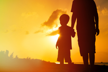silhouette of father and son holding hands at sunset sea