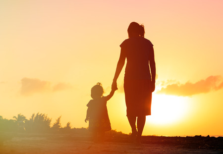 mother and little daughter walking on the beach at sunset