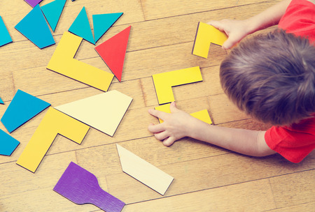 game play: little boy playing with puzzle, early education concept