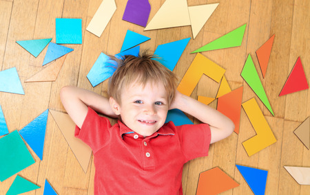 early learning: ni�o feliz con los juguetes del rompecabezas en el piso de madera, el aprendizaje temprano