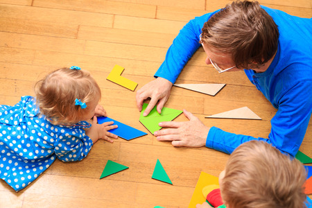 teacher and kids playing with geometric shapes, early learning photo