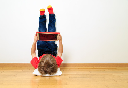little boy looking at touch pad at home