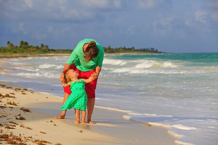 mother and little daughter walking on summer tropical beach photo