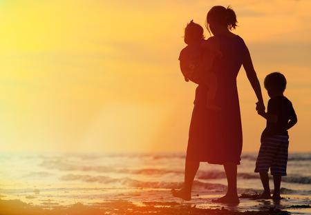 moeder en twee kinderen lopen op zand strand bij zonsondergang Stockfoto