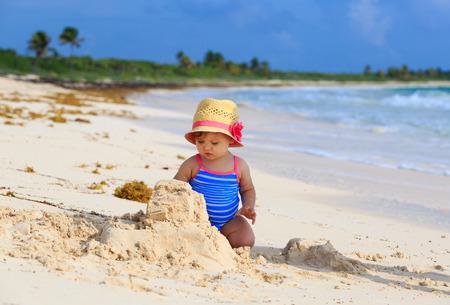 sandcastle: cute little girl building sandcastle on tropical beach Stock Photo