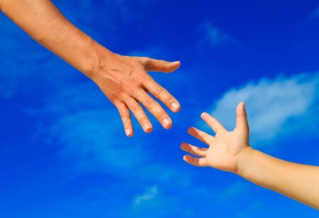 child protection: helping hand of mother and child on sky, care and protection Stock Photo
