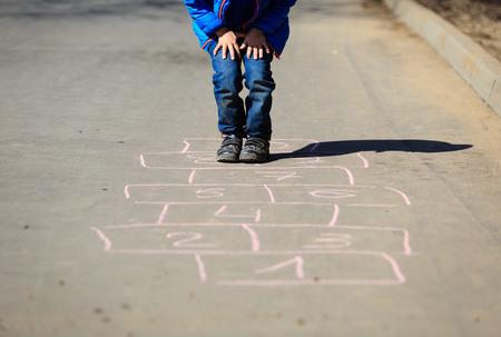 little boy playing hopscotch on driveway outside photo