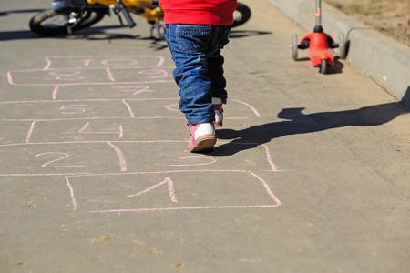 little girl playing hopscotch on asphalt outside photo